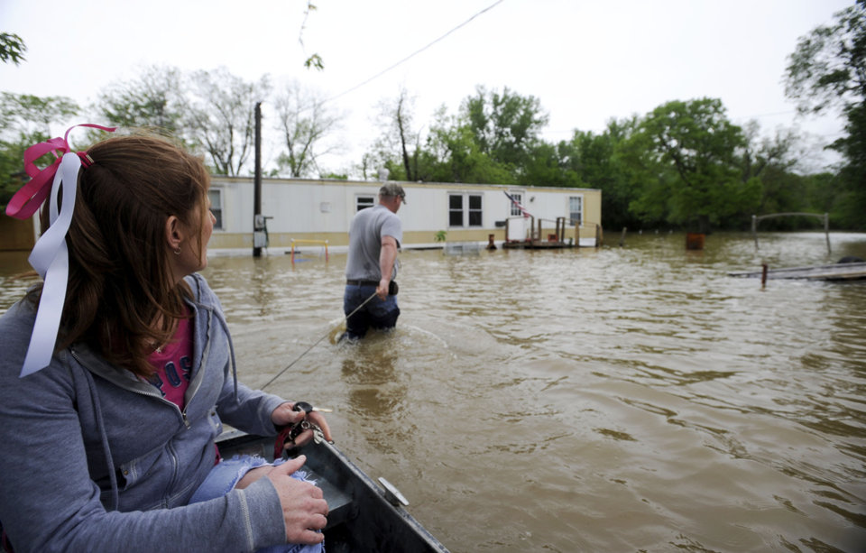 Photo - Kenny Back pulls his sister Jessica Capp in a boat to their family home to collect belongings in Old Shawneetown, Ill.  Wednesday, April 27, 2011.  With five days of heavy rainfall and more to come, volunteers filling sandbags Wednesday in southern Illinois towns threatened by the swollen Ohio River braced for possible record flooding. Officials asked for more volunteers to help with the effort. (AP Photo/The Southern, Stephen Rickerl)