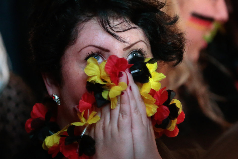 Photo - A German soccer fan reacts as she watches a live broadcast of the final match between Germany and Argentina at the soccer World Cup 2014 in Rio de Janeiro, Brazil, at a public viewing area called 'Fan Mile' in Berlin, Sunday, July 13, 2014. (AP Photo/Markus Schreiber)