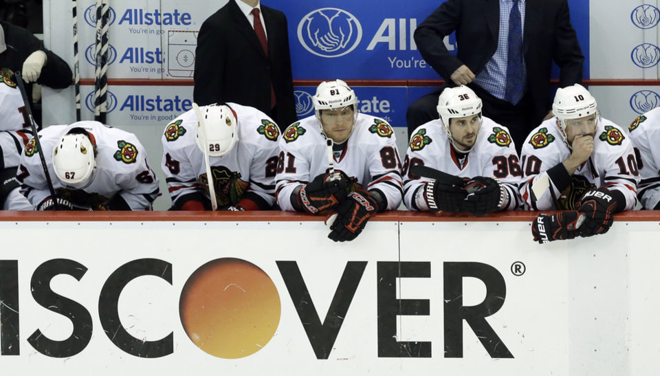 Photo - From left to right, Chicago Blackhawks Michael Frolik (67), Bryan Bickell (29), Marian Hossa (81), Dave Bolland (36) and Patrick Sharp (10) watch from the bench during the second period in Game 4 of the Western Conference semifinals  against the Detroit Red Wings in the NHL hockey Stanley Cup playoffs in Detroit, Thursday, May 23, 2013. Detroit won 2-0. (AP Photo/Paul Sancya)