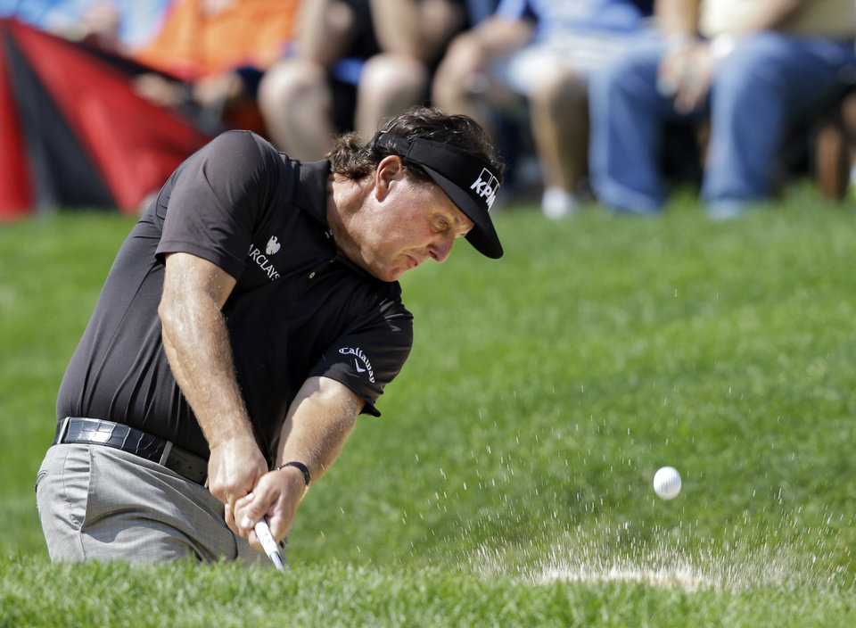 Photo - Phil Mickelson hits from the sand to the 15th green during the first round of the Bridgestone Invitational golf tournament Thursday, July 31, 2014, at Firestone Country Club in Akron, Ohio. (AP Photo/Mark Duncan)