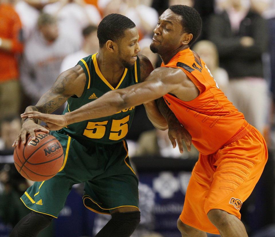 OSU's Brian Williams pressures Baylor's Pierre Jackson (55) in the second half of a men's college basketball game between the Oklahoma State University Cowboys and the Baylor University Bears at Gallagher-Iba Arena in Stillwater, Okla., Saturday, Feb. 4, 2012. Baylor beat OSU, 64-60. Photo by Nate Billings, The Oklahoman