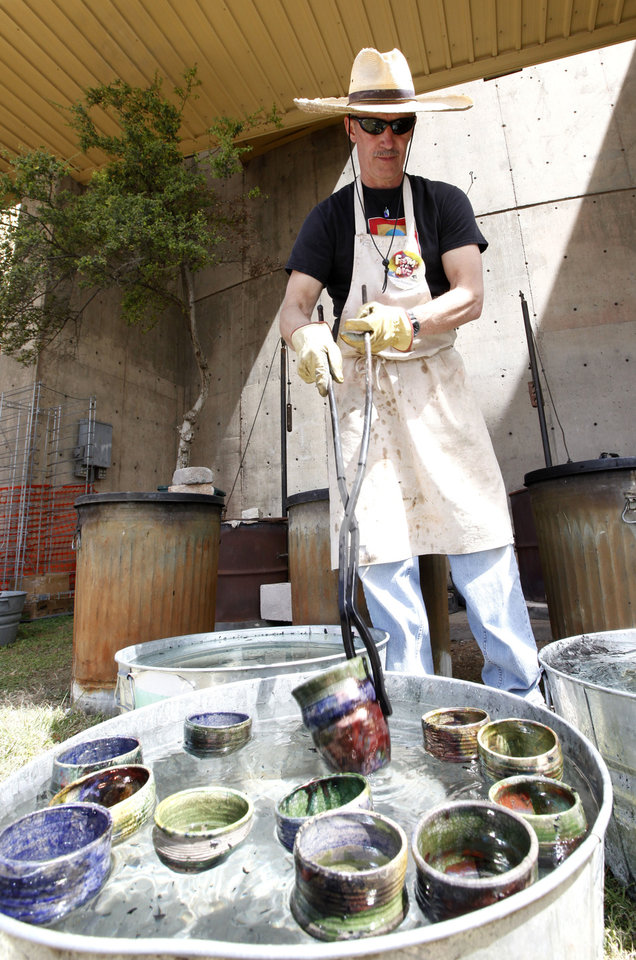 Collin Rosebrook, with Paseo Pottery, cools pottery mugs in water during the Festival of the Arts in downtown Oklahoma City, OK, Thursday, April 25, 2013,  By Paul Hellstern, The Oklahoman