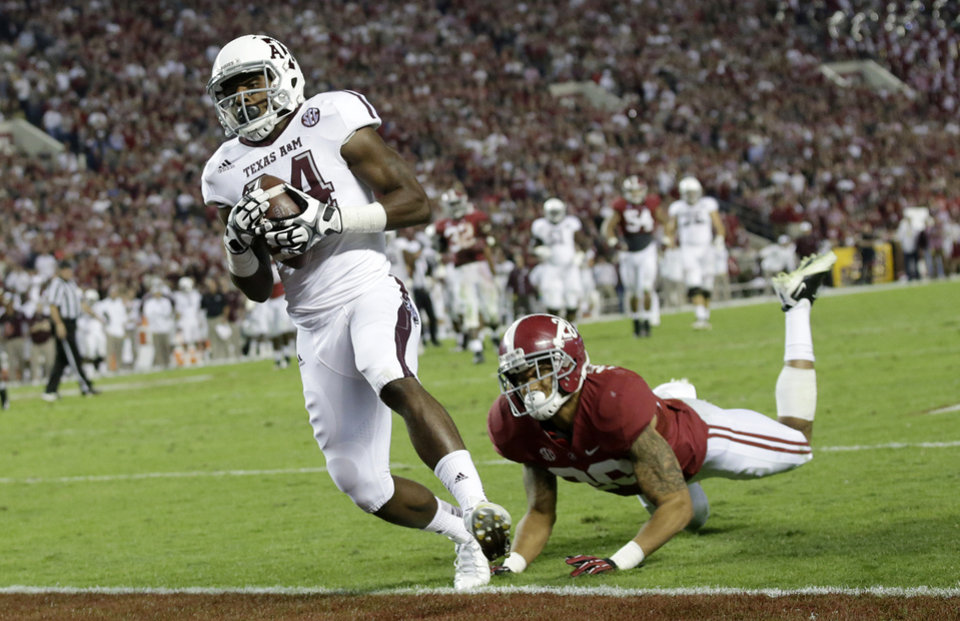 Texas A&M wide receiver Malcome Kennedy (84) catches the game winning touchdown as Alabama defensive back Dee Milliner (28) defends during the second half of an NCAA college football game at Bryant-Denny Stadium in Tuscaloosa, Ala., Saturday, Nov. 10, 2012. (AP Photo/Dave Martin)