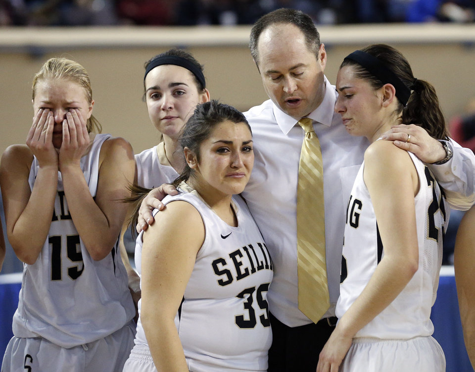 Photo - Seiling coach Brady Hamar comforts his team after the loss to Pond Ceek-Hunter in the Class A girls high school basketball state championship game between Seiling and Pond Creek-Hunter at the State Fair Arena in Oklahoma City, Okla., on Saturday, March 8, 2014.  Photo by Chris Landsberger, The Oklahoman