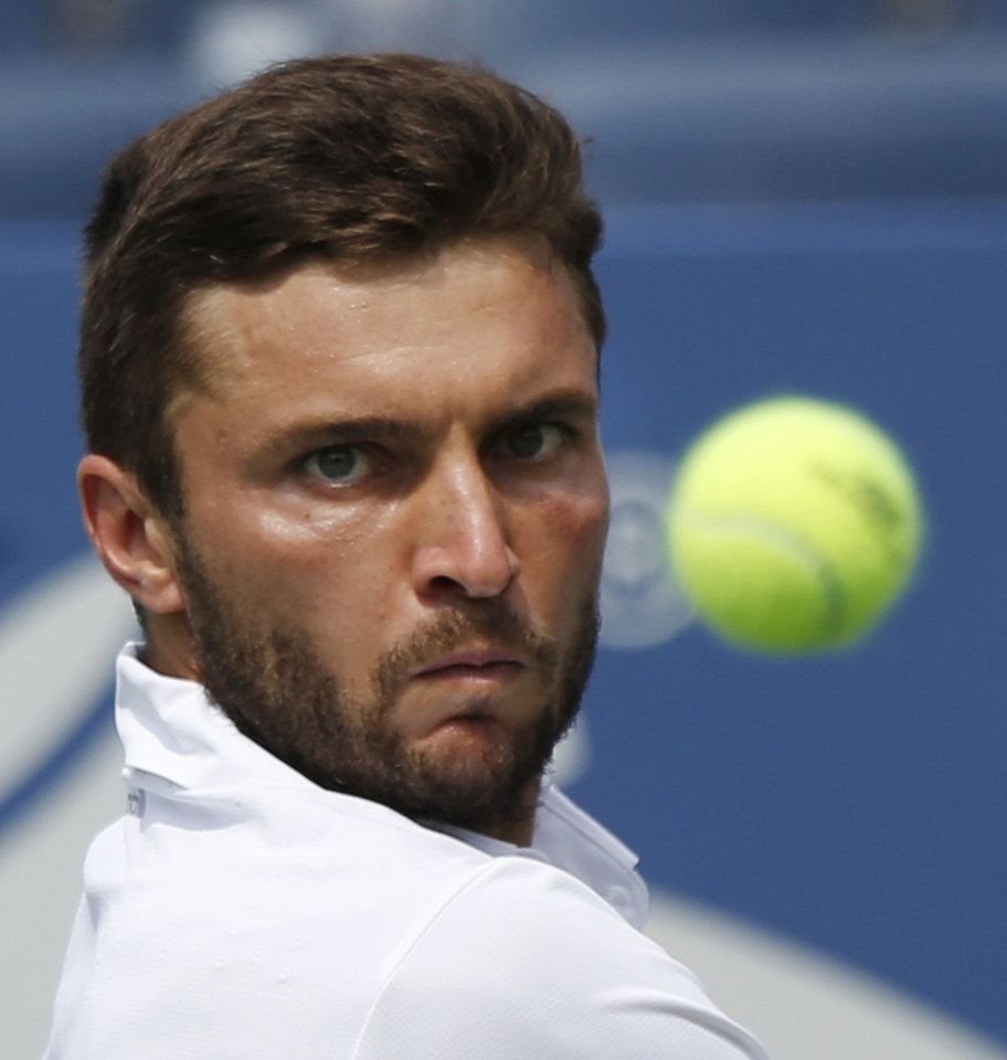 Photo - Gilles Simon, of France, returns a shot against David Ferrer, of Spain, during the third round of the 2014 U.S. Open tennis tournament, Sunday, Aug. 31, 2014, in New York. (AP Photo/Seth Wenig)