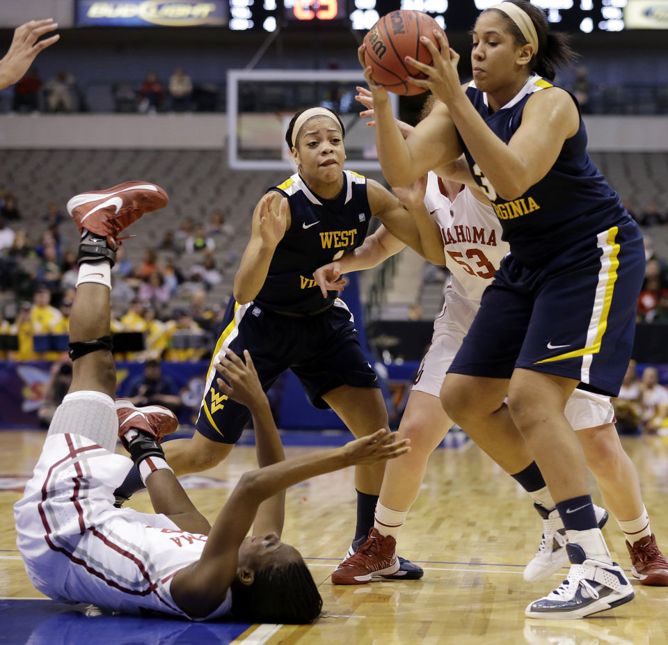 Oklahoma\'s Sharane Campbell, bottom left, loses control of the ball after falling to the court as West Virginia\' Ayana Dunning, top right, gains control in the first half of an NCAA college basketball game in the Big 12 women\'s tournament Saturday, March 9, 2013, in Dallas. Wester Virginia\' Christal Caldwell (1) and Oklahoma\' Joanna McFarland (53) watch during the play. (AP Photo/Tony Gutierrez)