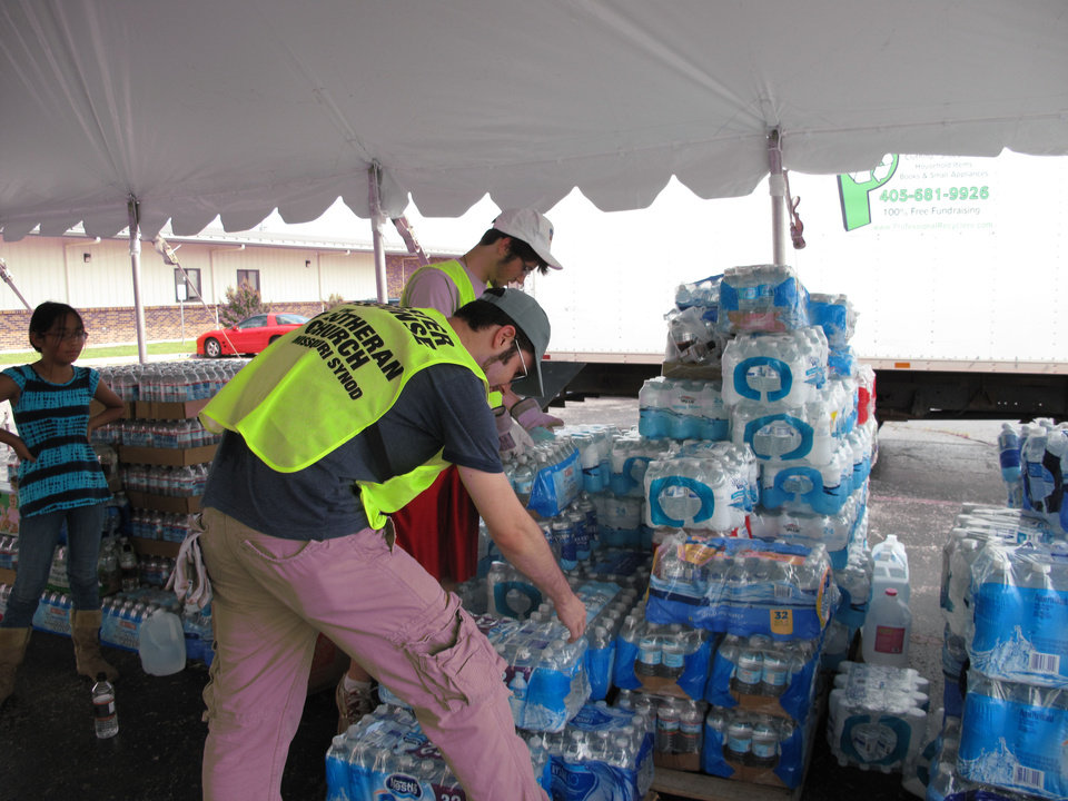 Brothers Austin and Parker Rupp, both of Edmond, stack donated bottled water under a tent in the parking lot of St. John's Lutheran Church, 1032 NW 12th Street in Moore. The church is a disaster relief distribution center to help tornado victims. Photo by Carla Hinton <strong>Carla Hinton - The Oklahoman</strong>