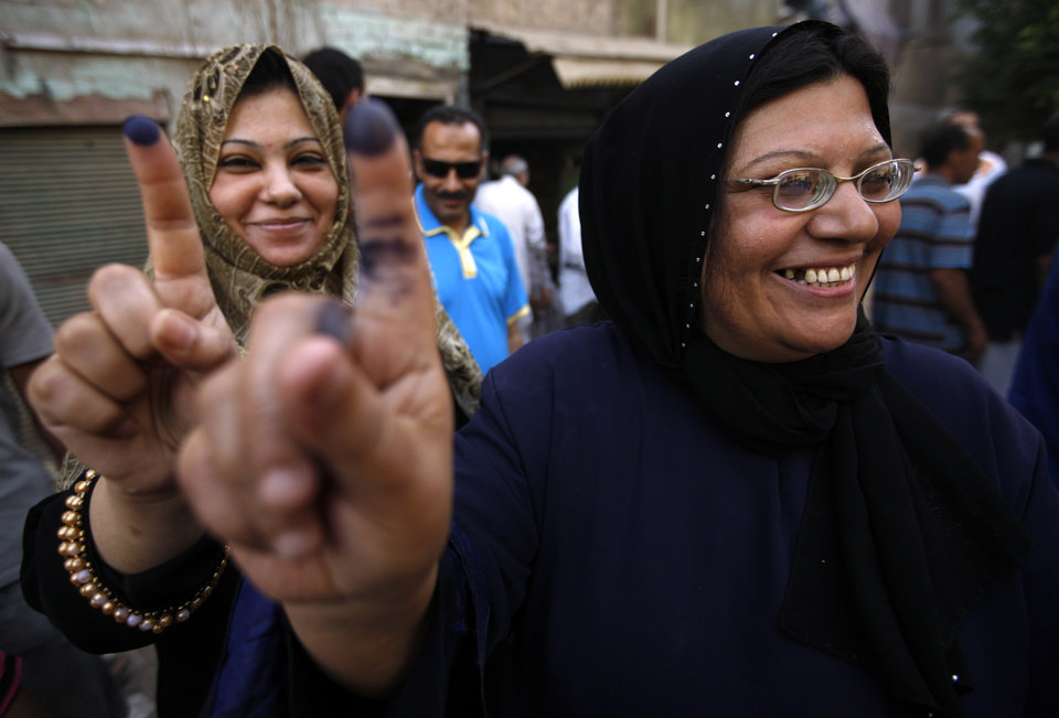 Two women show their inked fingers after casting their votes on the first day of the Presidential election at a polling center in Old Cairo, Egypt, Wednesday, May 23, 2012. More than 15 months after autocratic leader Hosni Mubarak's ouster, Egyptians streamed to polling stations Wednesday to freely choose a president for the first time in generations. Waiting hours in line, some debated to the last minute over their vote in a historic election pitting old regime figures against ascending Islamists. (AP Photo/Fredrik Persson) ORG XMIT: XFP121