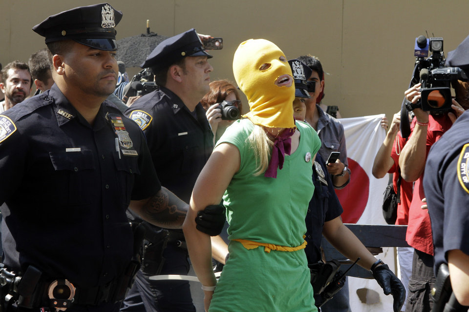 Photo -   A protester is arrested during a demonstration in front of the Russian consulate in support of Russian punk band Pussy Riot, Friday, Aug. 17, 2012 in New York. A Russian judge found three members of the provocative punk band guilty of hooliganism on Friday, in one of the most closely watched cases in recent Russian history. The judge said the three band members committed hooliganism driven by religious hatred and offending religious believers. The three were arrested in March after a guerrilla performance in Moscow's main cathedral calling for the Virgin Mary to protect Russia against Vladimir Putin, who was elected to a new term as Russia's president a few days later. (AP Photo/Alex Katz)