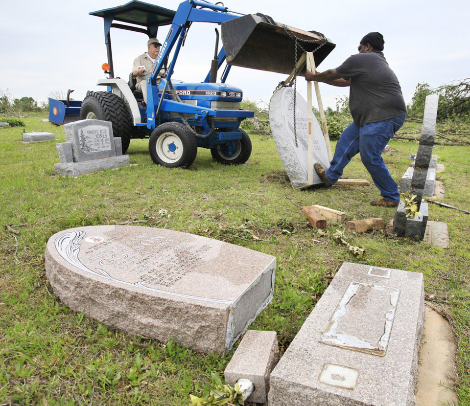 Workers use a front-end loader to upright a headstone toppled from its grave by Monday nights tornado in Earlsboro Cemetery on State Highway 9A in Pottawatomie County.  Photos by Jim Beckel, The Oklahoman