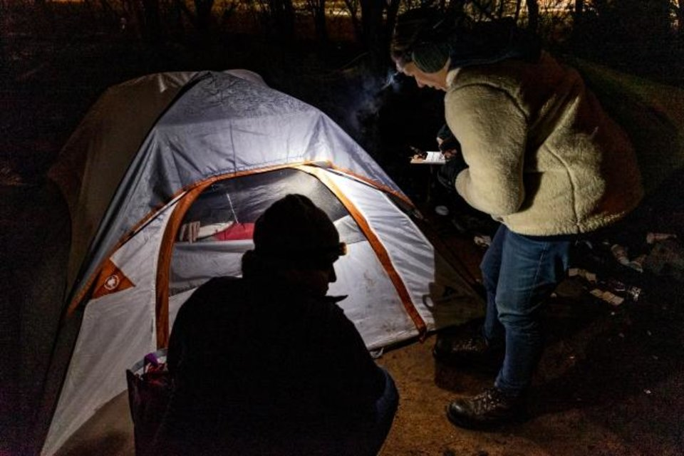Photo -  Amy Newberry and Theresa Seitz, from left, interview a person staying in a tent early. [Chris Landsberger/The Oklahoman]
