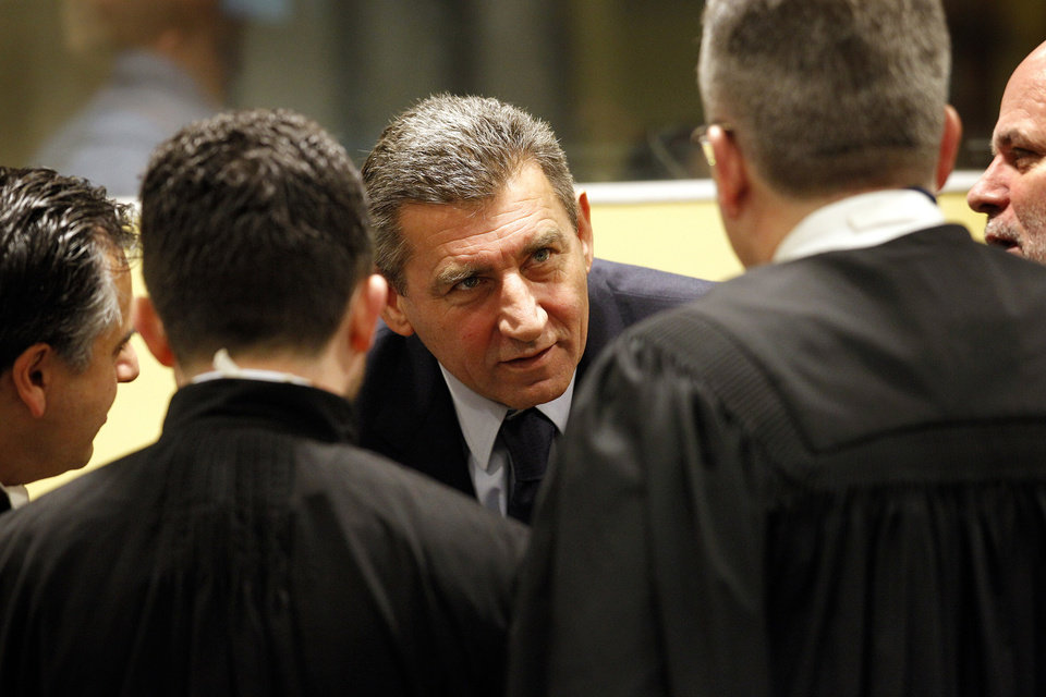 Former Croatian Army General Ante Gotovina, center, speaks with his lawyers in the courtroom of the Yugoslav war crimes tribunal (ICTY) prior to his appeal judgement in The Hague, Netherlands, Friday, Nov. 16, 2012. The ICTY is delivering its decision in the appeal of two Croatian generals convicted for their roles in a 1995 military offensive to drive Serb rebels out of land they had occupied for years along part of Croatia's border with Bosnia. Ante Gotovina and Mladen Markac, were sentenced to 24 and 18 years respectively in 2011 for war crimes and crimes against humanity. (AP Photo/Bas Czerwinski, Pool)