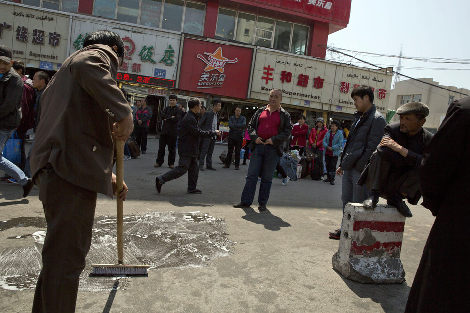 "Photo - Men wash and scrub the site of the Wednesday explosion outside the Urumqi South Railway Station in Urumqi in northwest China's Xinjiang Uygur Autonomous Region on Thursday, May 1, 2014.  Chinese President Xi Jinping demanded ""decisive"" action against terrorism after a slashing and bomb attack at a Xinjiang train station killed three people and injured 79 while the leader was wrapping up a tour of the far-western region. (AP Photo/Ng Han Guan)"