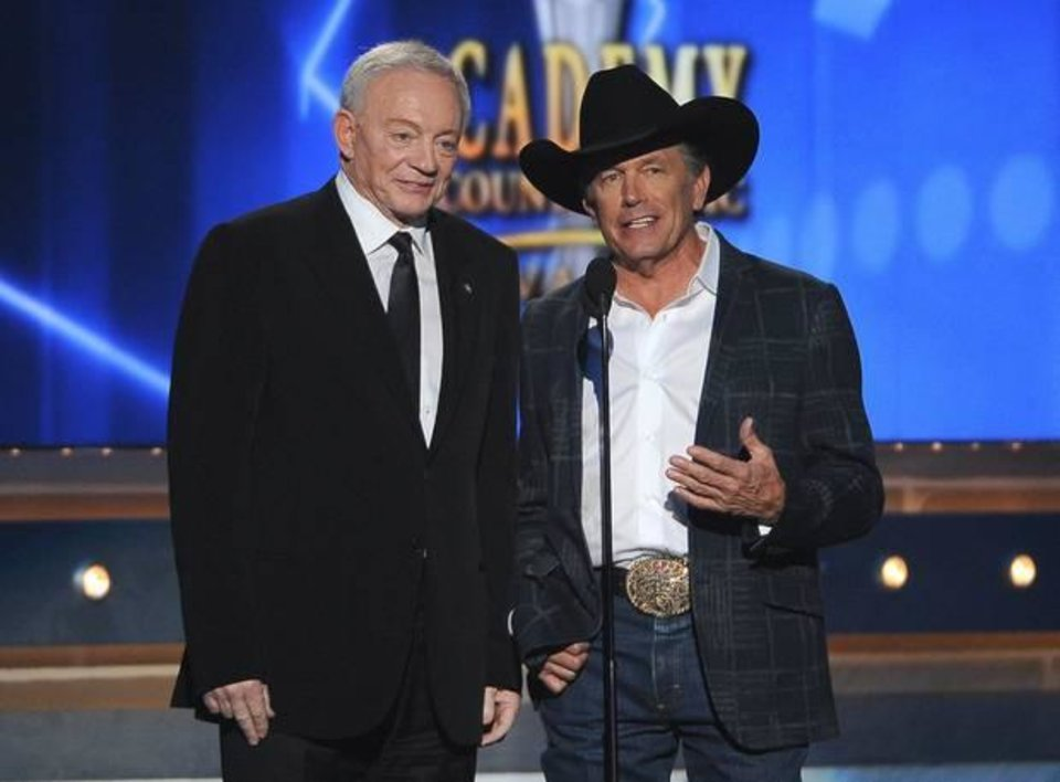 Photo -  Jerry Jones, left, and George Strait speak on stage at the 49th annual Academy of Country Music Awards at the MGM Grand Garden Arena on Sunday, April 6, 2014, in Las Vegas. (AP)