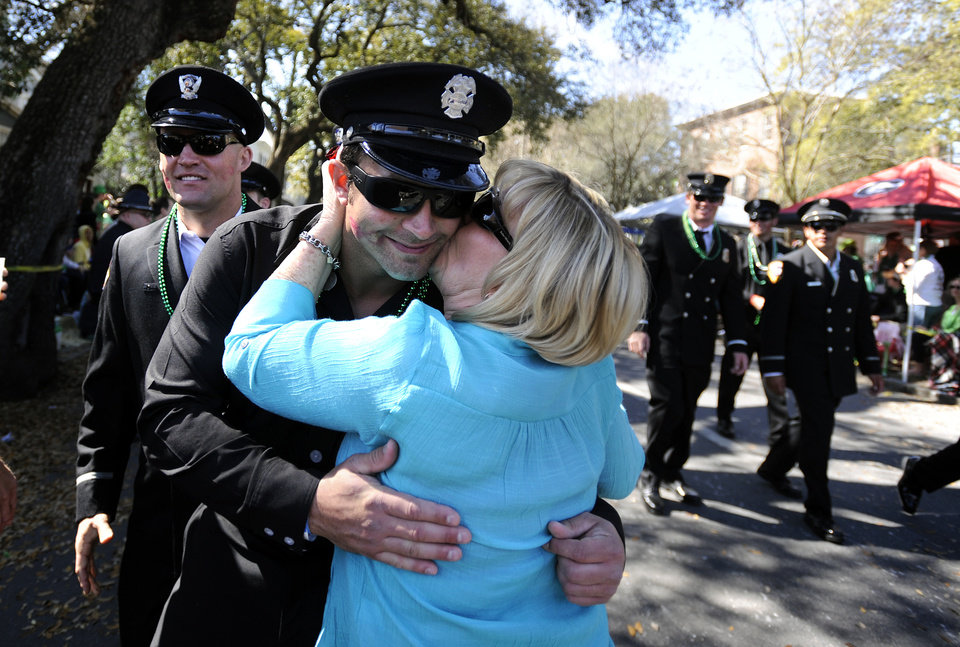 Photo - Firefighter Steve Ortiz of the Los Angels City Fire Department is kissed while marching in the St. Patrick's Day parade, Saturday, March 16, 2013, in Savannah, Ga. Led by bagpipers in green kilts, the parade snaked through the streets with more than 300 floats, marching bands, military units marching in formation, and dignitaries in convertibles decorated with shamrocks. (AP Photo/Stephen Morton)