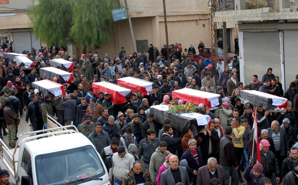 Photo - In this photo released by the Syrian official news agency SANA, Syrian citizens carry the coffins wrapped by Syrian flags for the victims who were killed Thursday by a car bomb, during their funeral processions, at al-Kaffat village in the central Hama province, Syria, Friday, Jan. 10, 2014. Rebel-on-rebel fighting between an al-Qaida-linked group and an array of more moderate and ultraconservative Islamists has killed nearly 500 people over the past week in northern Syria, an activist group said Friday, in the most serious bout of violence among opponents of President Bashar Assad since the civil war began. (AP Photo/SANA)