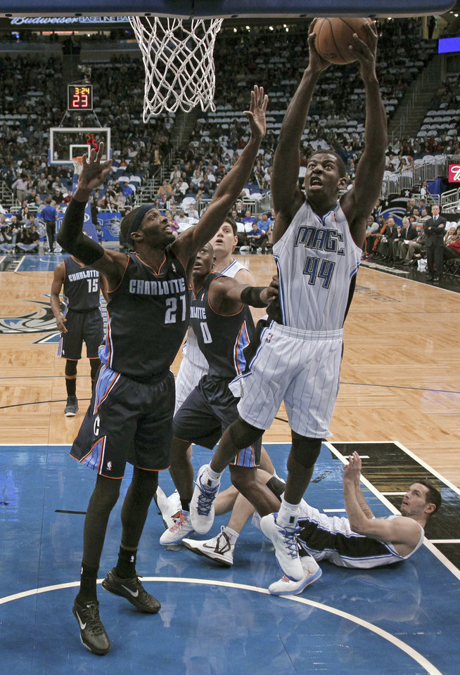 Photo - Orlando Magic's Andrew Nicholson (44) takes the ball to the basket past Charlotte Bobcats' Hakim Warrick (21) during the first half of an NBA basketball game, Friday, Jan. 18, 2013, in Orlando, Fla. (AP Photo/John Raoux)