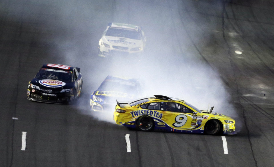 Photo - Marcos Ambrose (9) spins as AJ Allmendinger is engulfed in smoke during the NASCAR Sprint Cup series Coca-Cola 600 auto race at the Charlotte Motor Speedway in Concord, N.C., Sunday, May 25, 2014. Ryan Truex avoids the collision at left. (AP Photo/Gerry Broome)