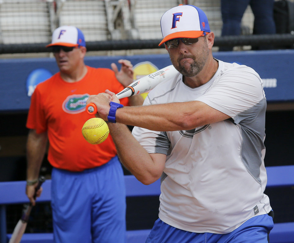 Photo - Florida head coach Tim Walton hits a ball during the Women's College World Series media day at ASA Hall of Fame Stadium on Wednesday, May 28, 2014 in Oklahoma City, Okla.  Photo by Chris Landsberger, The Oklahoman