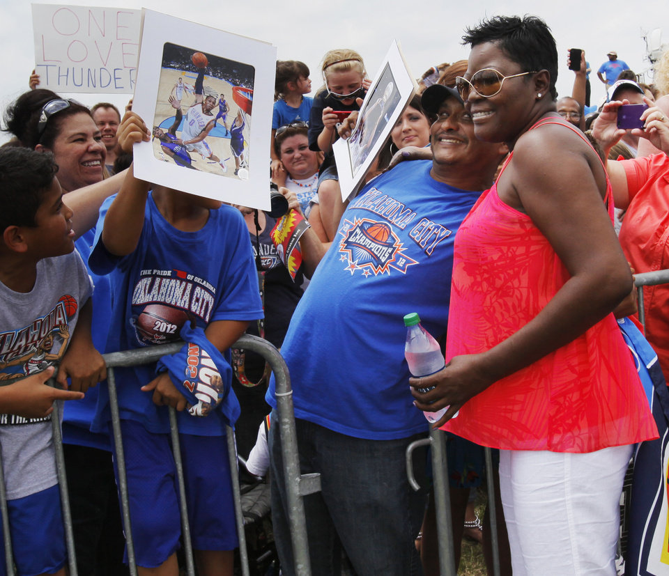 Photo - Wanda Pratt, Kevin Durant's mother, poses for a photo with Jose Romero while waiting for the team to arrive during a welcome home rally for the Oklahoma City Thunder in a field at Will Rogers World Airport after the team's loss to the Miami Heat in the NBA Finals, Friday, June 22, 2012. Photo by Nate Billings, The Oklahoman