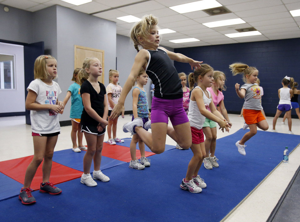 Photo - Ella Hodges, 7, takes a leap at a cheer and tumbling camp this week sponsored by Norman's Parks and Recreation Department. PHOTO BY STEVE SISNEY, THE OKLAHOMAN  STEVE SISNEY