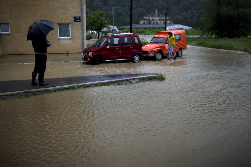 Photo - A man stands on a flooded street in heavy rain in a suburb of Belgrade, Serbia, Thursday, May 15, 2014. Hundreds of people have been evacuated from their homes as floods caused by heavy rains gripped the Balkans Thursday, overflowing roads, bridges and railways, closing down schools, and cutting off power supplies and phone lines. (AP Photo/Marko Drobnjakovic)