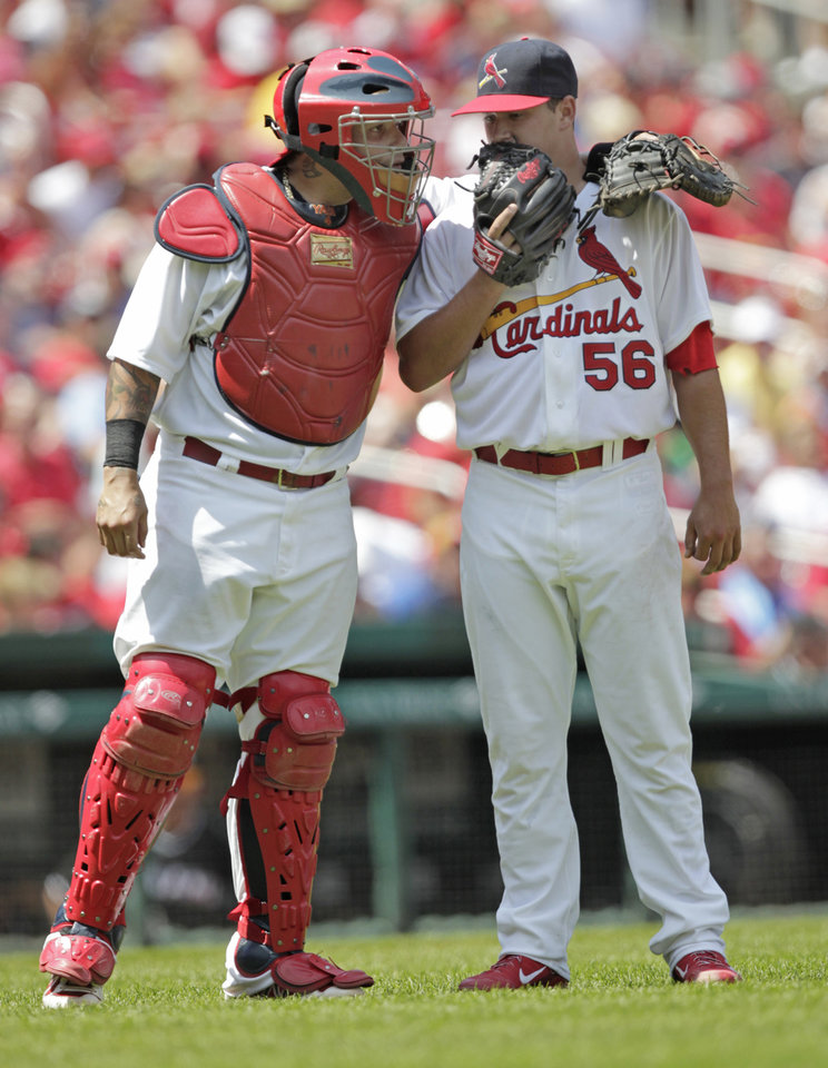 Photo - St. Louis Cardinals catcher Yadier Molina, left, talks with starting pitcher Marco Gonzales, right, in the fifth inning of a baseball game against the Miami Marlins, Sunday, July 6, 2014 in St. Louis. (AP Photo/Tom Gannam)