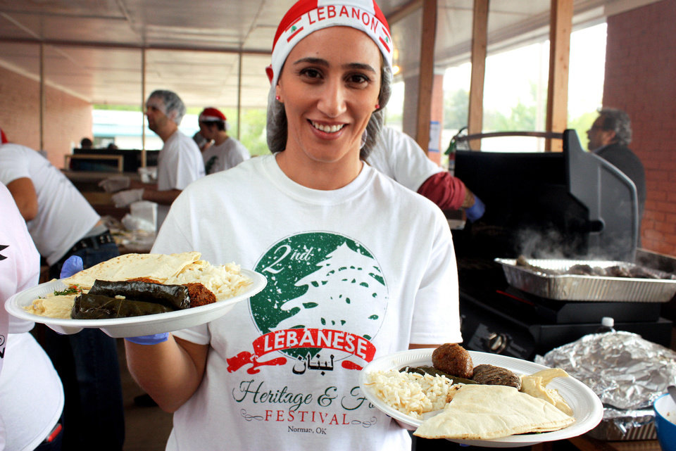 Claudine Rayess-Elya serves plates of traditional Lebanese food at the Lebanese Heritage Festival sponsored by Our Lady of Lebanon Maronite Catholic Church. PHOTO BY LYNETTE LOBBAN, FOR THE OKLAHOMAN