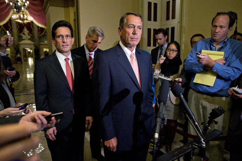 Photo - House Majority Leader Rep. Eric Cantor, R-Va., left, and House Majority Whip Rep. Kevin McCarthy, R-Calif., rear center, look on as Speaker of the House Rep. John Boehner, R-Ohio, pauses during a news conference on Capitol Hill on Tuesday, Oct. 1, 2013 in Washington. Congress was unable to reach a midnight deadline to keep the government funded, triggering the first government shutdown in more than 17 years. (AP Photo/Evan Vucci)