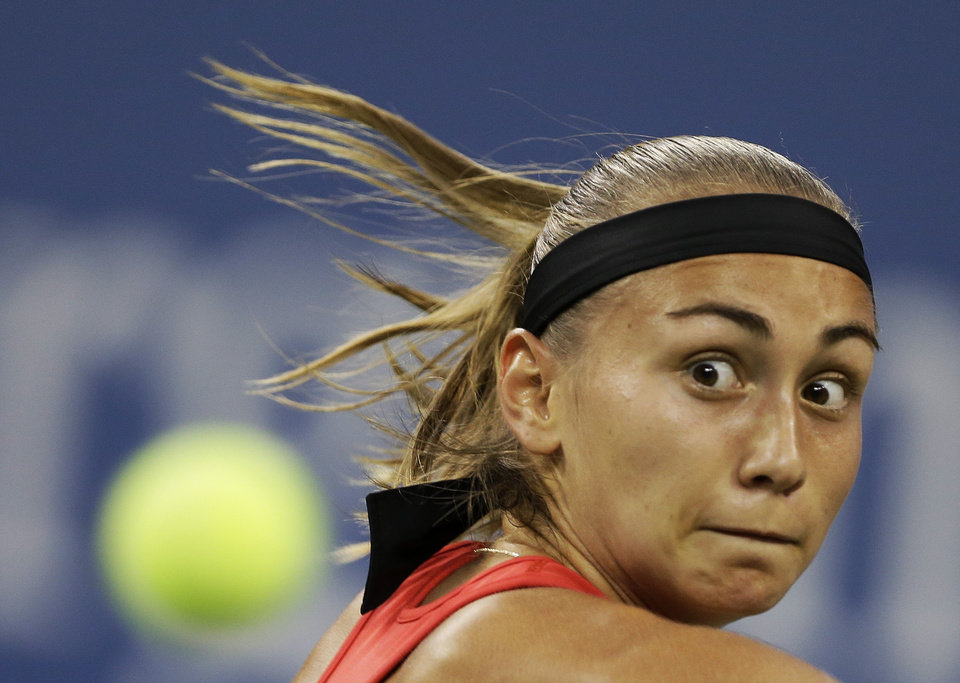 Photo - Aleksandra Krunic, of Serbia, returns a shot to Victoria Azarenka,  of Belarus, during the fourth round of the 2014 U.S. Open tennis tournament Monday, Sept. 1, 2014, in New York. (AP Photo/Darron Cummings)