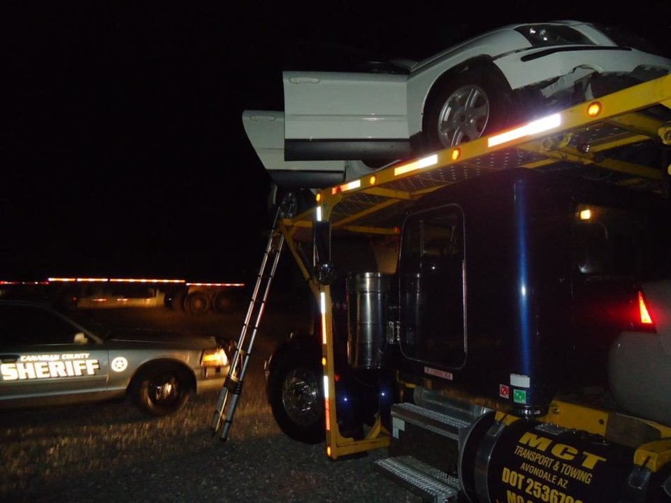 Photo - The car where Canadian County Sheriff's deputies found nearly 77 pounds of cocaine sits with its doors open on a tractor-trailer.  PHOTO PROVIDED BY CANADIAN COUNTY SHERIFF'S OFFICE   -  Canadian County Sheriff's office