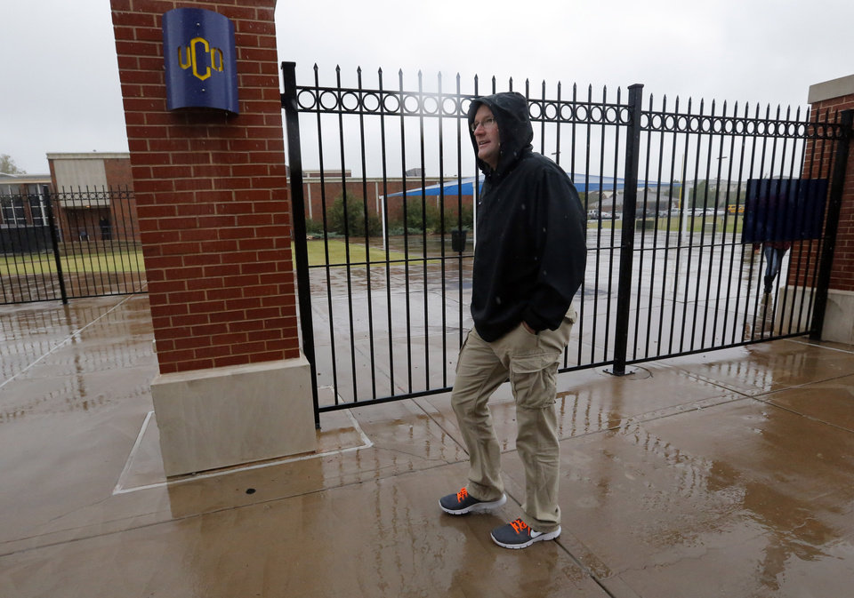 Photo - Edmond Public Schools' Athletic Director Mike Nunley walks in the rain at Wantland Stadium before a game, Thursday, Sept. 13, 2012. Photo by Sarah Phipps, The Oklahoman