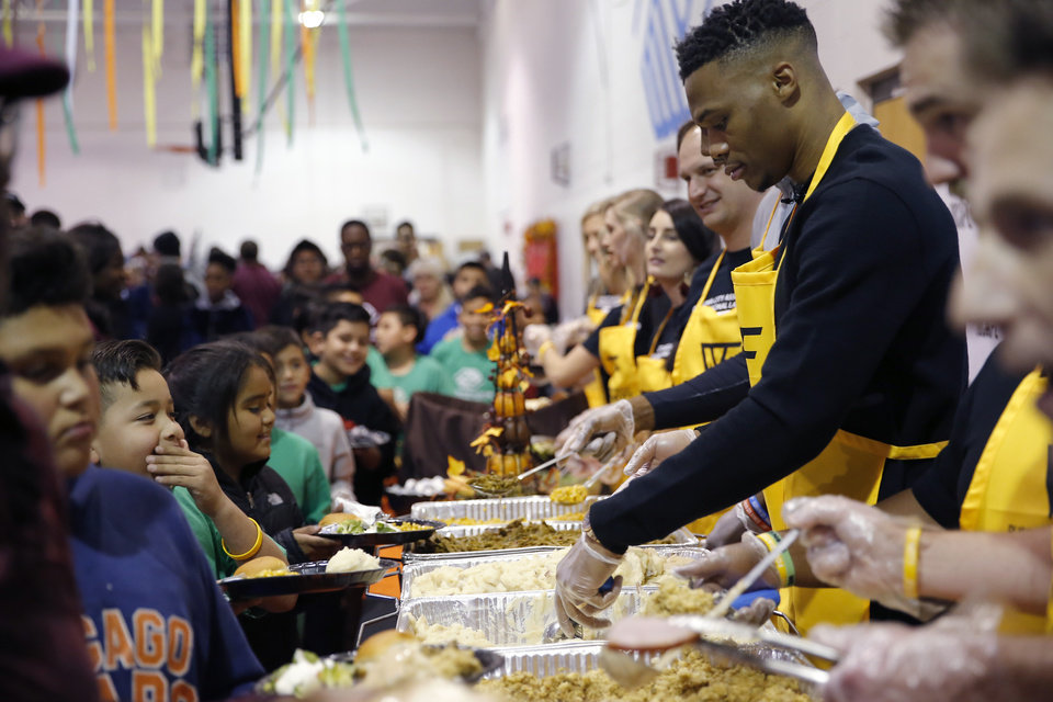 Photo - Oklahoma City's Russell Westbrook serves mashed potatoes during Russell Westbrook's Why Not? Foundation Hosts 7th Annual Thanksgiving Dinner at the Boys & Girls Clubs of Oklahoma County in Oklahoma City,  Nov. 15, 2018. Photo by Sarah Phipps, The Oklahoman