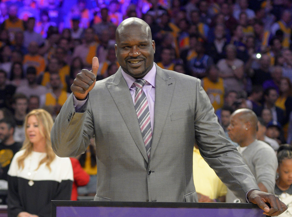 FILE - In this April 2, 2013, file photo, former Los Angeles Lakers center Shaquille O'Neal gestures during ceremonies to retire his jersey during halftime of an NBA game between the Lakers and Dallas Mavericks, in Los Angeles. O'Neal is joining the ownership group of the Sacramento Kings. The Kings announced Monday, Sept. 23, 2013, that O'Neal has acquired a minority stake in the team under new owner Vivek Ranadive. The Kings will introduce the four-time NBA champion at a news conference Tuesday in Sacramento. (AP Photo/Mark J. Terrill, File)