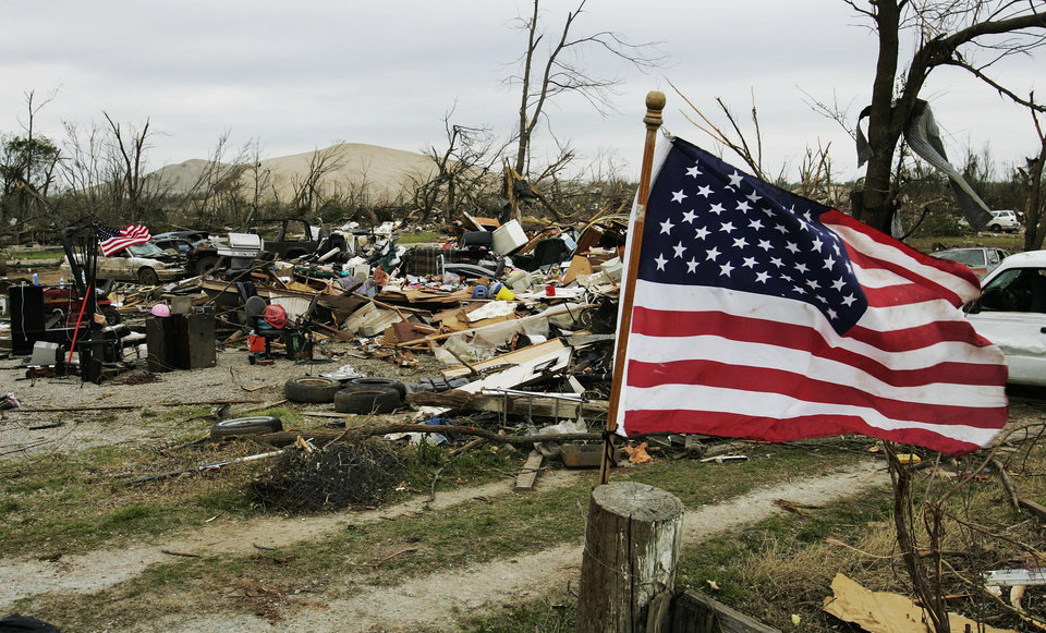 Photo - TORNADO DAMAGE: Flags fly at a tornado damaged home in Picher, Okla., Tuesday, May 13, 2008. No government money will be awarded for rebuilding any of the 100 homes leveled by a deadly tornado that tore through one of the nation's most polluted areas, state and federal officials said Tuesday on a tour of the region.  Saturday's tornado was responsible for seven deaths in Picher. The severe weather killed another 20 people in the Plains and the Southeast. (AP Photo/Sue Ogrocki) ORG XMIT: OKSO104