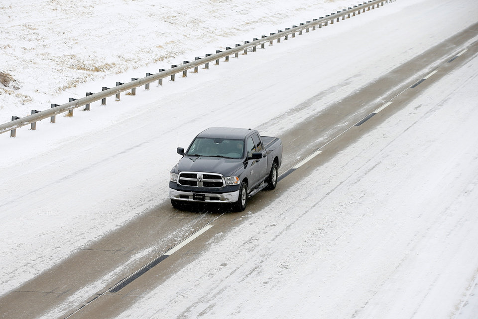 Photo - A vehicle travels west on the John Kilpatrick Turnpike during a winter storm in Oklahoma City, Sunday, Feb. 14, 2021. [Bryan Terry/The Oklahoman]