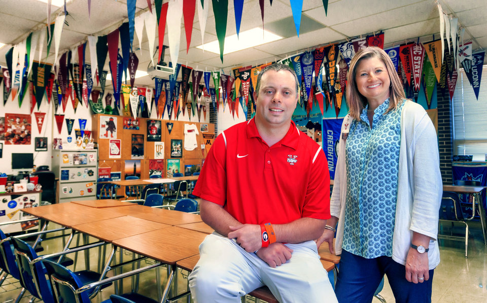 Photo - Yukon Middle School 6th Grade Academy geography teacher, Daniel Griswold, poses for a photo with principal Diana Lebsack in his classroom filled with college swag he has collected to inspire students to pursue higher education in Yukon, Okla. on Thursday, Aug. 9, 2018.   Photo by Chris Landsberger, The Oklahoman