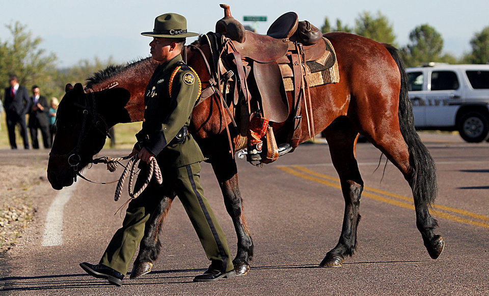 Photo -   U.S. Border Patrol agent Nicholas Ivie's riderless horse with boots set backward in honor of the slain agent is seen during the funeral procession on Monday, Oct. 8, 2012, at the Church of Jesus Christ of Latter Day Saints in Sierra Vista, Ariz. The head of the U.S. Border Patrol agents' union says the agent was killed when he apparently opened fire on two colleagues thinking they were armed smugglers and was killed when they returned fire. (AP Photo/Arizona Daily Star,Mike Christy ) ALL LOCAL TV OUT; PAC-12 OUT; MANDATORY CREDIT