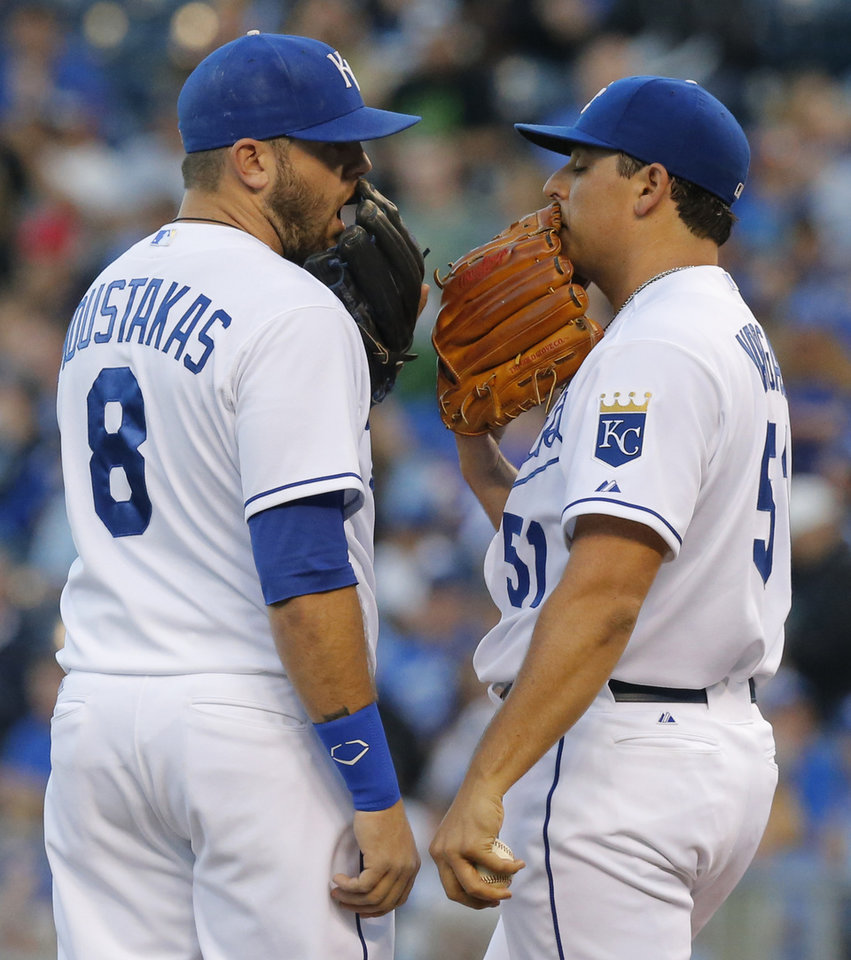 Photo - Kansas City Royals third baseman Mike Moustakas (8) talks with starting pitcher Jason Vargas, right, between batters during the first inning of a baseball game against the Minnesota Twins at Kauffman Stadium in Kansas City, Mo., Friday, April 18, 2014. (AP Photo/Orlin Wagner)