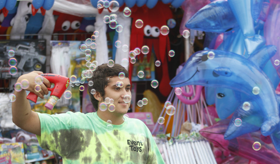 Photo - George Lohman demonstrates how to use the Bubble Gun during the opening day of the Oklahoma State Fair at State Fair Park in Oklahoma City, Thursday  September  13, 2012. Photo By Steve Gooch, The Oklahoman