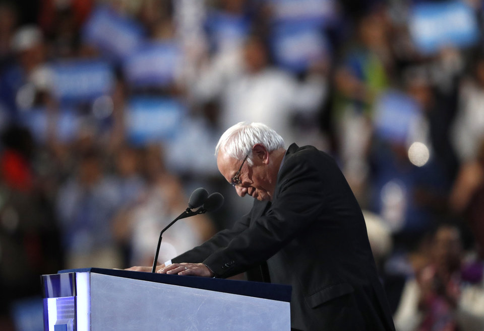 Photo - Former Democratic Presidential candidate, Sen. Bernie Sanders, I-Vt., stands at the podium as he is greeted by massive applause during the first day of the Democratic National Convention in Philadelphia , Monday, July 25, 2016. (AP Photo/Paul Sancya)