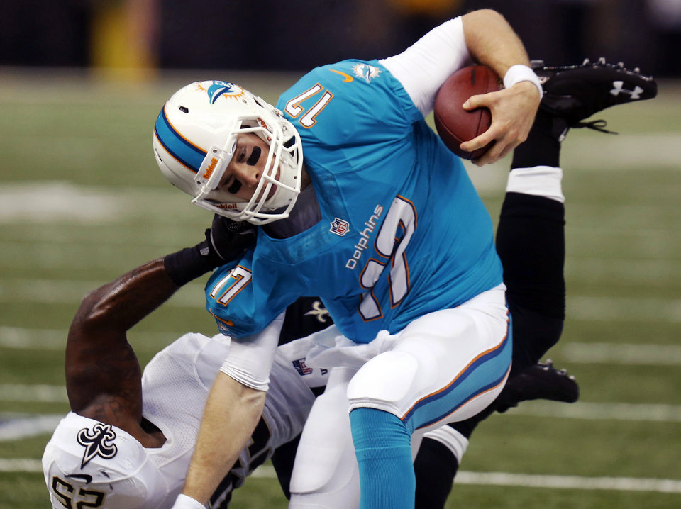 Photo - Miami Dolphins quarterback Ryan Tannehill (17) is dragged down by New Orleans Saints defensive back Rafael Bush (25) in the first half of an NFL football game in New Orleans, Monday, Sept. 30, 2013. (AP Photo/Bill Haber)