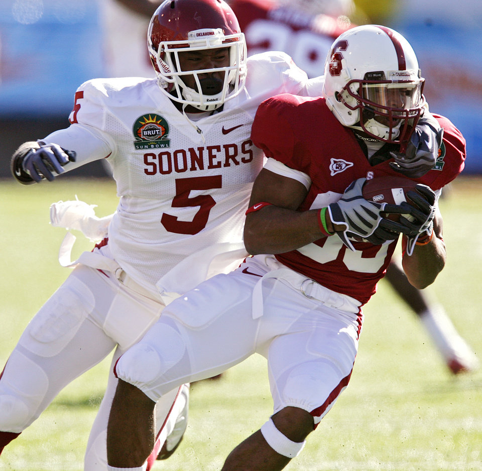 Oklahoma's Joseph Ibiloye (5) brings down Stanford's Doug Baldwin (89) during the first half of the Brut Sun Bowl college football game between the University of Oklahoma Sooners (OU) and the Stanford University Cardinal on Thursday, Dec. 31, 2009, in El Paso, Tex.   Photo by Chris Landsberger, The Oklahoman