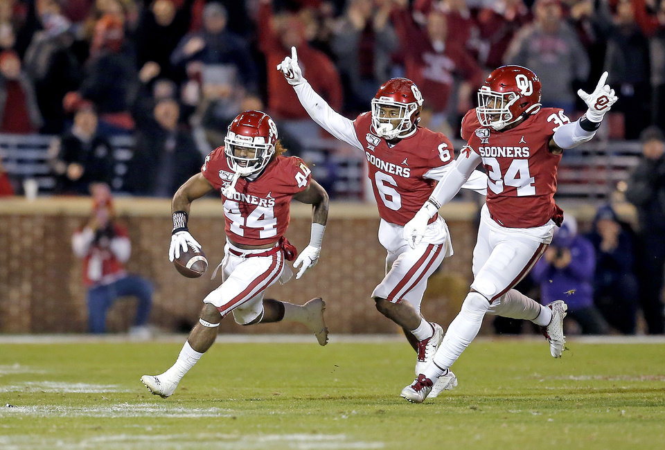 Photo - Oklahoma's Brendan Radley-Hiles (44) celebrates his interception with Tre Brown (6) and David Ugwoegbu (34) late in the fourth quarter during an NCAA football game between the University of Oklahoma Sooners (OU) and the TCU Horned Frogs at Gaylord Family-Oklahoma Memorial Stadium in Norman, Okla., Saturday, Nov. 23, 2019. OU won 28-24. [Sarah Phipps/The Oklahoman]