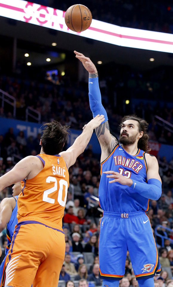 Photo - Oklahoma City's Steven Adams (12) shoots the ball over Phoenix's Dario Saric (20) during the NBA basketball game between the Oklahoma City Thunder and the Phoenix Suns at the Chesapeake Energy Arena in Oklahoma City , Friday, Dec. 20, 2019.   [Sarah Phipps/The Oklahoman]