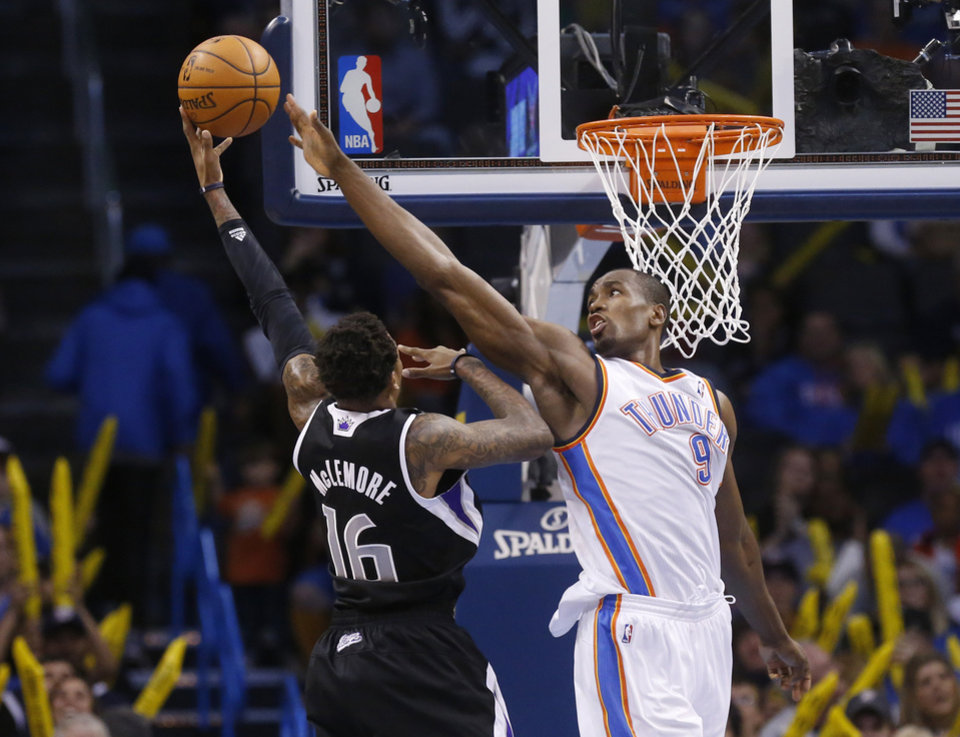 Photo - Oklahoma City Thunder forward Serge Ibaka (9) defends as Sacramento Kings guard Ben McLemore (16) shoots in the fourth quarter of an NBA basketball game in Oklahoma City, Sunday, Jan. 19, 2014. Oklahoma City won 108-93. (AP Photo/Sue Ogrocki)