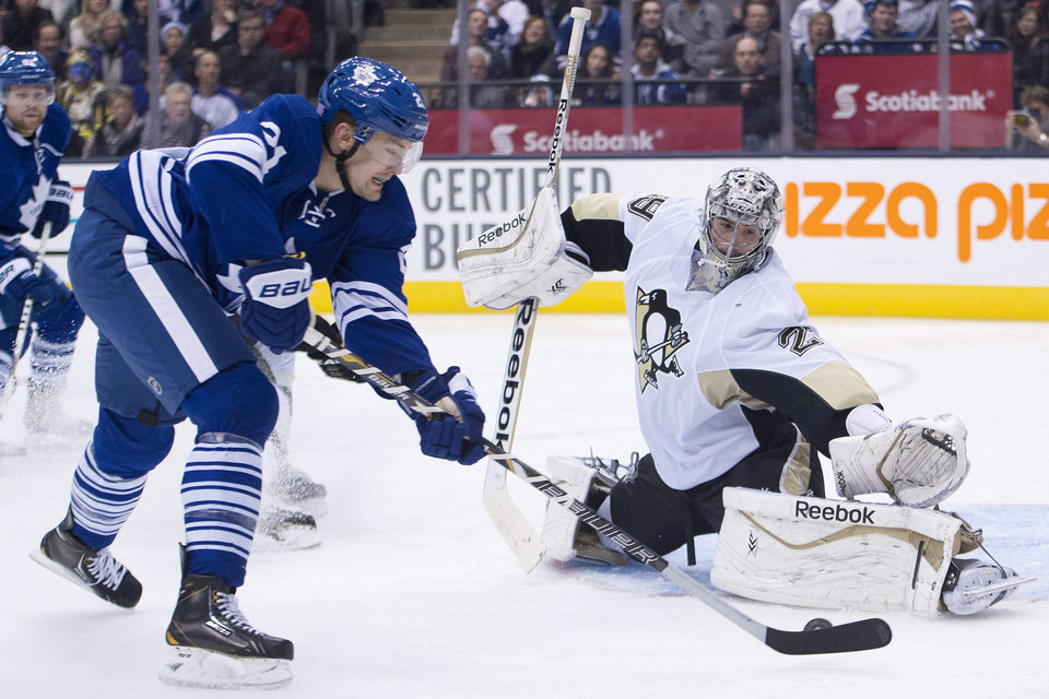 Photo - Toronto Maple Leafs forward James van Riemsdyk, left, gets stopped by Pittsburgh Penguins goalie Marc-Andre Fleury, right, during the second period of an NHL hockey game, Saturday, Oct. 26, 2013 in Toronto. (AP Photo/The Canadian Press, Nathan Denette)
