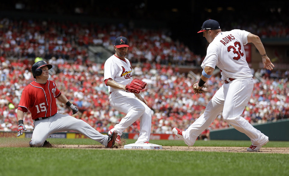 Photo - Washington Nationals' Nate McLouth, left, is safe at first as he beats St. Louis Cardinals first baseman Matt Adams, right, to the bag and Cardinals' Jaime Garcia watches during the fifth inning of a baseball game on Sunday, June 15, 2014, in St. Louis. (AP Photo/Jeff Roberson)