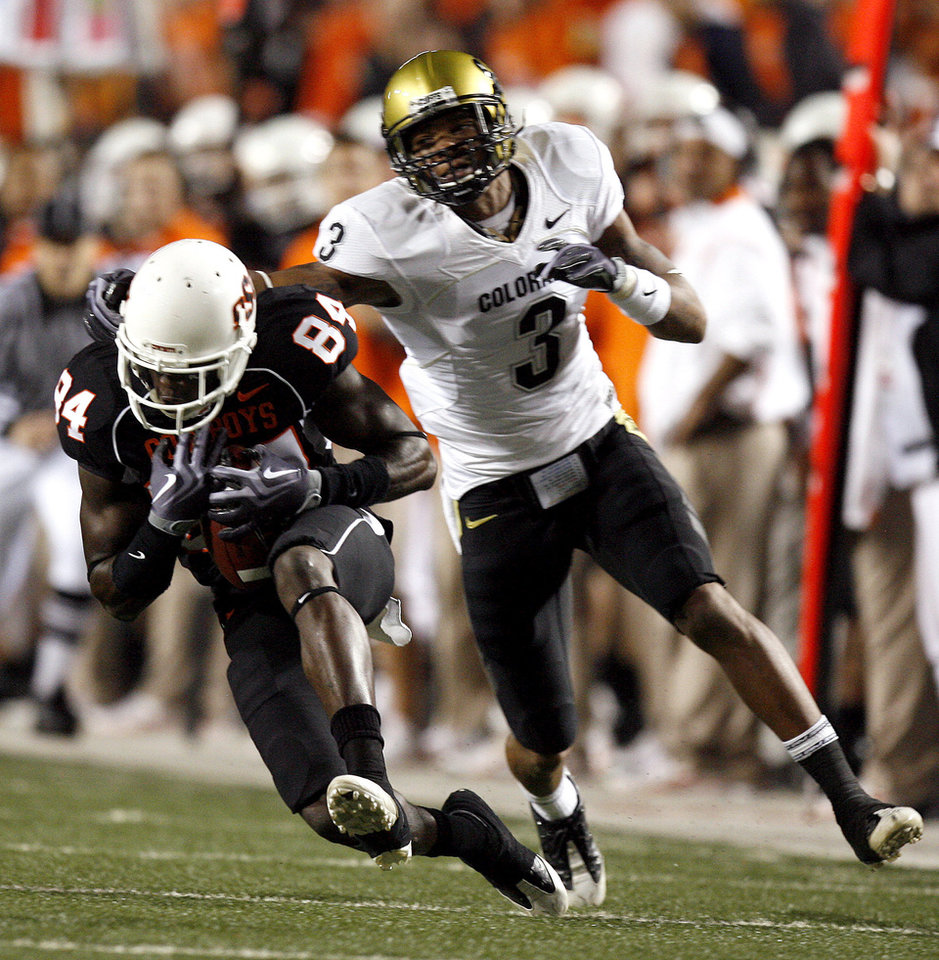 Photo - OSU's Hubert Anyiam (84) catches a pass as Colorado's Jimmy Smith (3) tries to tackle him during the college football game between Oklahoma State University (OSU) and the University of Colorado (CU) at Boone Pickens Stadium in Stillwater, Okla., Thursday, Nov. 19, 2009. Photo by Sarah Phipps, The Oklahoman