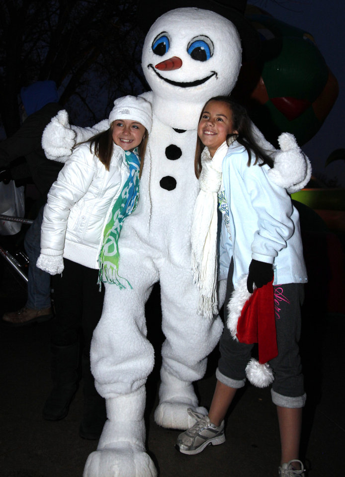 Right: A snowman hugs Kyla Vogel and Elizabeth Duncan at last year's city-sponsored Holiday Celebration at Andrews Park.